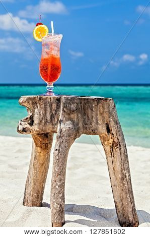 Glass of red drink is on the original beach table Maldives The Indian Ocean