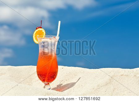 Glass of red drink in scorching desert