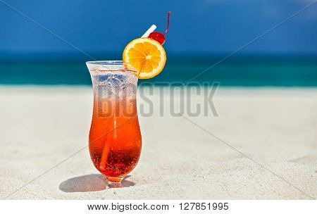 Glass of cocktail is on sandy coral beach Maldives The Indian Ocean