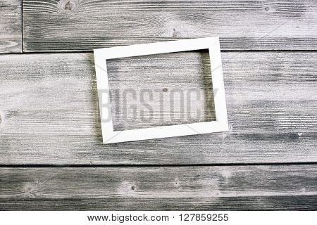 See-through frame hanging on wooden wall. Mock up
