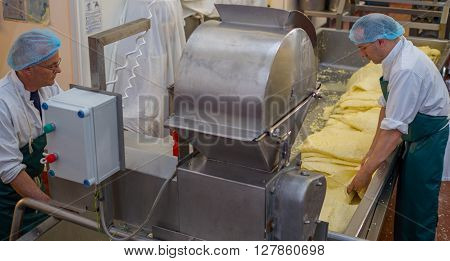 Men processing cheese inside a factory using a mill in which they shred blocks of cheese for packing