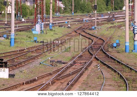 Railways with wooden sleepers poles grass and turnouts at summer day