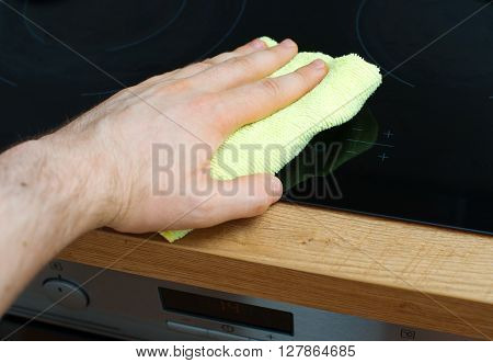 Man's Hand Wipes Cooktop In The Kitchen.
