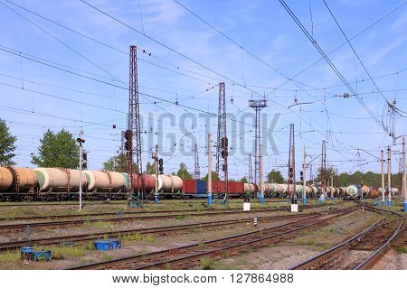 Freight train with tanks moves on rusty railway at sunny summer day