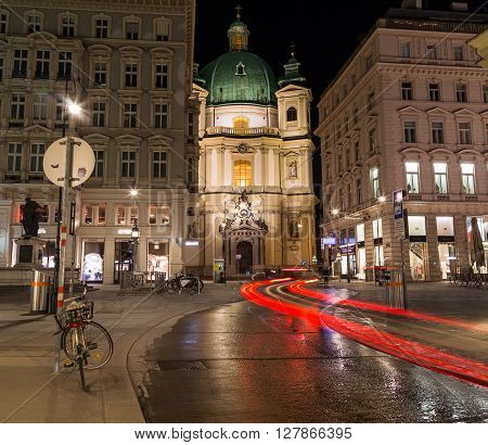 VIENNA AUSTRIA - 22ND APRIL 2016: The outside of the Catholic Church of St. Peter in Vienna at night from the Graben. Trails from traffic can be seen.