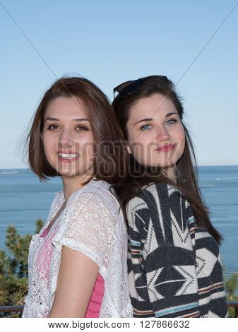 Two Girl On Beach Back To Back Smiling
