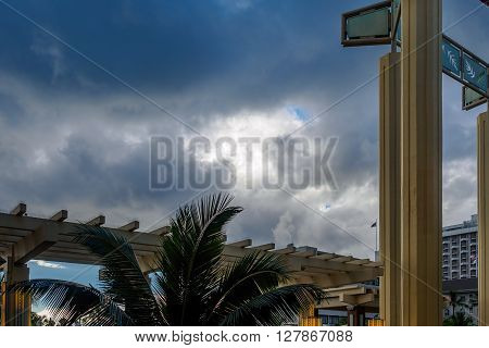 Honolulu, Hawaii, USA - Dec 15, 2015: Pillars and dramatic sky as viewed from the atrium of the Hyatt Regency Waikiki Beach Resort and Spa Hotel. This area is open to the public and is often busy with people walking around since a swimming pool is nearby.