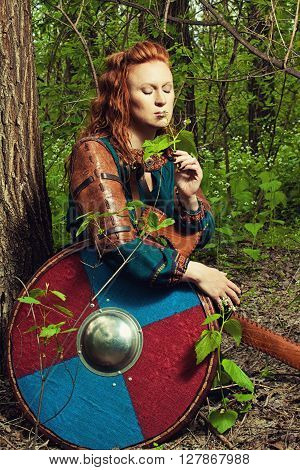 Pretty redhead scandinavian woman sitting in a forest