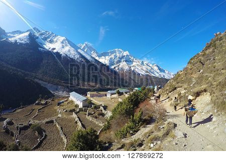 Nepalese porter (sherpa), low paid hard and dangerous job, trekking in Himalaya scenery, peaceful landscape with fields and valley on sunny summer day, small mountain village, trek to Everest, Nepal ** Note: Visible grain at 100%, best at smaller sizes