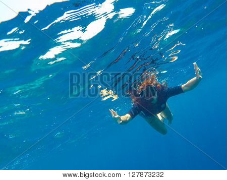 A woman underwater in black swimsuit and mask, loose hair girl snorkeling in mask, red hair young girl diving, girl snorkel in blue sea, tropical sea vacation holiday summer activity, girl on vacation