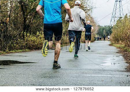 group of runners men running down road in Park. feet in mud