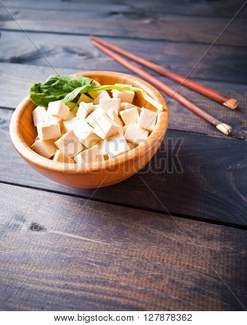 Bowl of raw tofu cubes spinach and chopsticks on wooden background