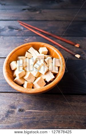 Bowl of raw tofu cubes and chopsticks on wooden background. Ingredient for vegan cuisine