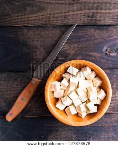 Bowl of raw tofu cubes and knife on rustic wooden background
