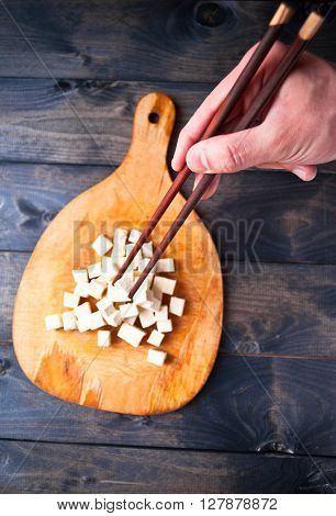 Cubes of raw tofu on shabby cutting board and man's hand with two chopsticks