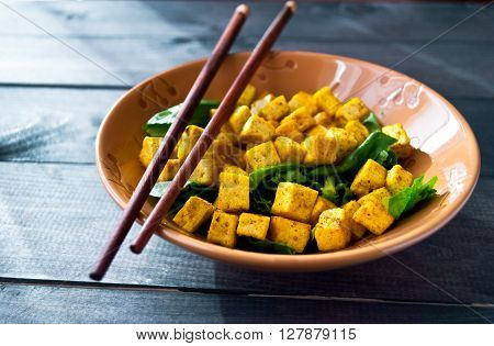 Salad from fried tofu with curry and fresh spinach in brown ceramic bowl with chopsticks