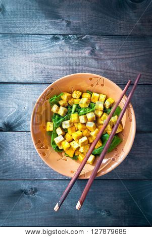 Salad from fried tofu with curry and fresh spinach served in brown bowl with chopsticks on wooden background. Space for text