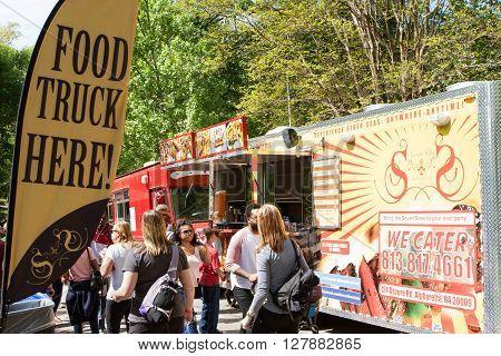 ATLANTA, GA - APRIL 2016:  A sign announces the presence of food trucks to a crowd attending the Food-o-rama festival in Grant Park in Atlanta GA on April 16 2016 .