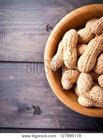 Bowl of fried peanuts with nutshell on shabby wooden background