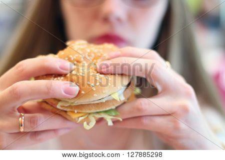 Woman eats fresh appetizing hamburger in cafe focus on hamburger shallow dof