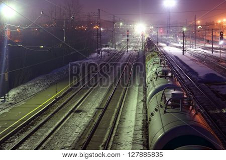 Top view of freight train with tanks on railways at winter night