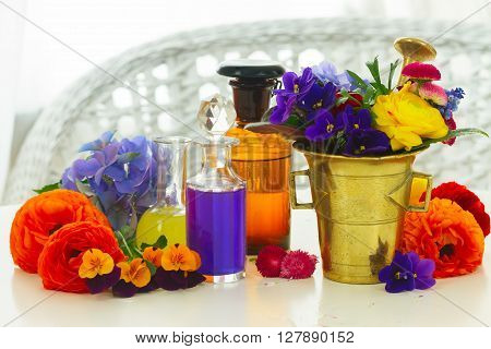 Flowers, mortar and bottles of potions, herbal medicine concept