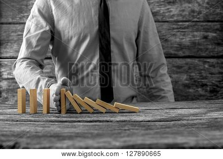Greyscale image of businessman stopping falling dominos with his hand with selective colour of the dominos.