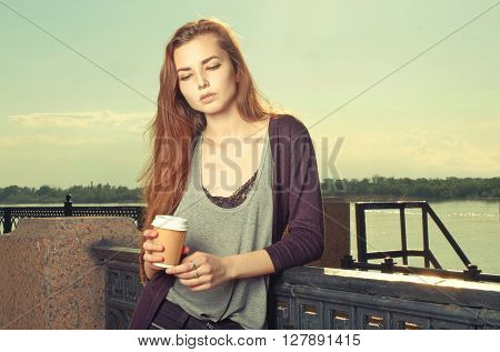 Portrait of beautiful brown haired girl standing and looking down. She keeping takeaway drink. Urban city scene. Outdoors portrait vintage film color imitation. Instagram-like toned image, colorized