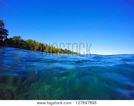 Summer beach landscape through sea water, clean blue sea water look through, snorkel sight to the green beach, summer vacation on the beach, seaside view to tropical island, turquoise sea shore life