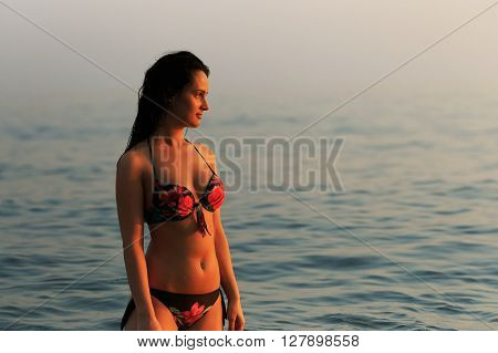 Attractive Woman Enjoying The Sunrise With Ocean In Background.
