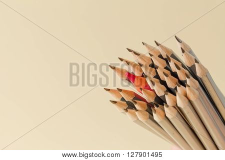 Celebratory pencil among usual pencils beige background