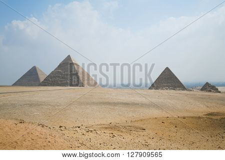landmark of three pyramids in Giza next to Cairo city Egypt Africa the Great Pyramid of Khufu from year 2500 Before Christ and pyramids of Khafre and Menkaure pharaohs