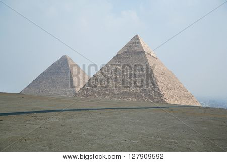 landmark of two pyramids in Giza next to Cairo city Egypt Africa the pyramid of Khafre pharaoh and behind the Great Pyramid of Khufu from year 2500 Before Christ