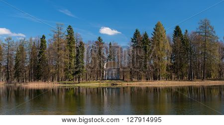 St. Petersburg, Gatchina Park, Pavilion of Eagle Island at White Lake. Trees and the pavilion reflected in the water.
