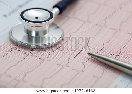 Stethoscope Head And Silver Pen Lying On Cardiogram