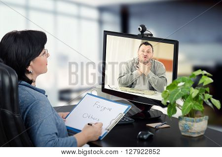 Mentally disordered middle-aged man has online psychotherapy session. Certified psychiatrist sits and hears in front of monitor with irritated man. Psychiatrist has just written message for him. She is able to help him to resolve anger issues. poster