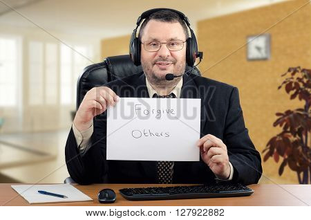 Portrait online psychiatrist. Middle-aged man in black suit sits at the desk and holds written message - Forgive Others. Psychiatrist wearing a headset. He works with patients through internet. Horizontal indoors shot.