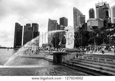 SINGAPORE - MAY 19, 2014: Merlion statue with skyscrapers at the background and people around. It is a symbol of the city which attracts many tourists located in Merlion Park. Black and white
