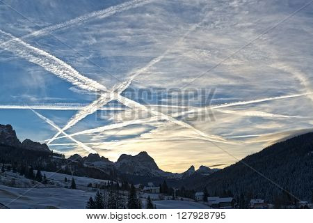 beautiful winter sunrise in the italian mountains and cloudy sky with aircraft contrails Dolomiti