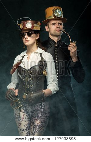 Steampunk couple. Man with a pipe and a girl with glasses and hat. Victorian woman and man in alternative history.