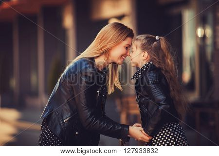 Fashion family concept - stylish mother and child wear. A portrait of a happy family: a young beautiful woman with her little cute daughter.