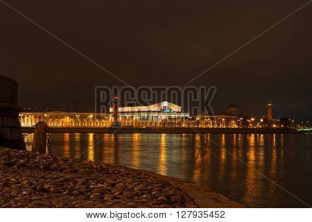 View on Vasilevsky Island - Stock Exchange Building and Rostral columns. Night Photography. In the foreground, Palace Embankment, boat ramp.
