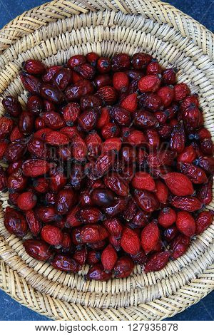 Scuttle full of dried, red rose hips