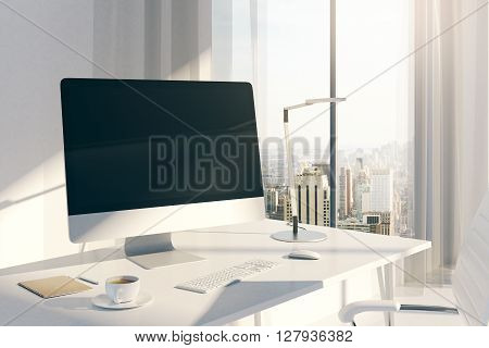 Sideview of creative desktop with blank computer screen in sunlit office with windows curtains and city view. Mock up 3D Rendering