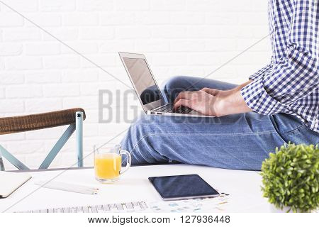 Sideview of businessman with notebook on his lap sitting on office desktop with white brick wall in the background