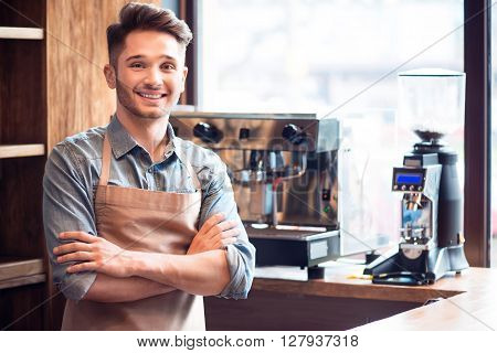 With positivity in mind. Pleasant delighted barista smiling and folding his hands while standing in the cafe