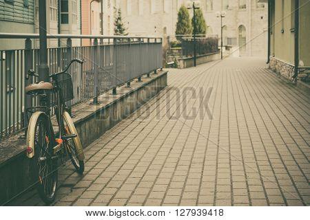 Urban scene with retro bike on empty street vintage toned image