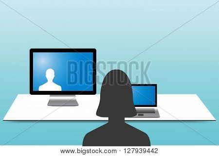 Silhouette of the woman is looking at a man communicating with her rom a monitor standing on the table before her. Woman has a tablet on the table before her.