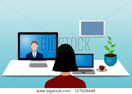 Woman is looking at a man communicating with her rom a monitor standing on the table before her. Woman has a tablet, potted plant and red cup of coffee are on the table before her. Blank bulletin board is hanging on the wall.