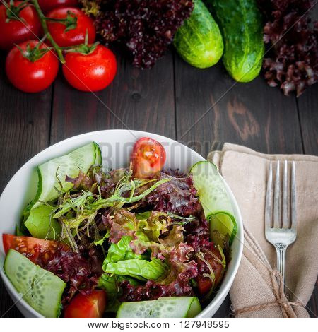 Fresh vegetable salad, healthy food, organic cucumbers, tomatoes and salad leaves